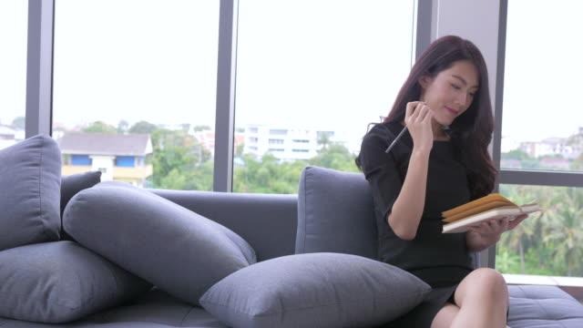 frau geschäftsidee auf merkzettel schreiben. asiatische geschäftsfrau auf notizblock mit stift schreiben. - menschlicher finger stock-videos und b-roll-filmmaterial