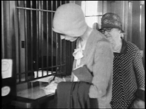 b/w 1927 woman writing check at ticket booth of early airline / senior woman next to her / newsreel - newsreel stock videos and b-roll footage