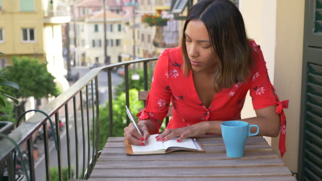 A woman writing in a journal diary traveling in a luxury resort town in Italy, Europe. - Slow Motion
