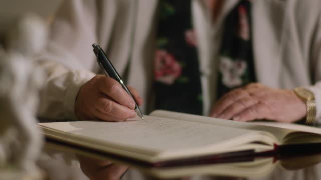 vidéos et rushes de une femme écrivant dans un cahier - carnet