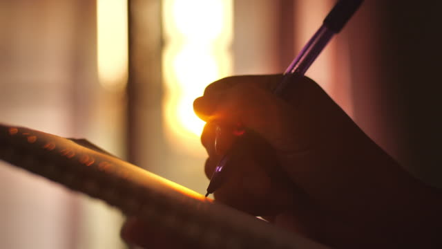 woman writing in her diary at sunset - diary stock videos & royalty-free footage