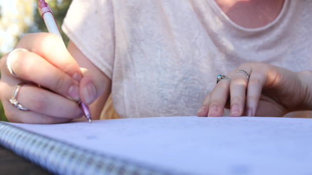 woman writing in notebook, close up, exterior - nur junge frauen stock-videos und b-roll-filmmaterial