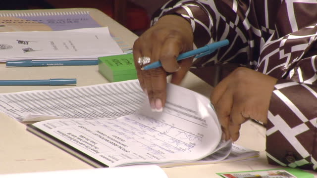 CU, Woman writing in registration paperwork at polling place, Toledo, Ohio, USA