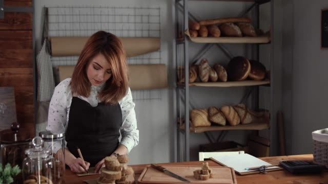 woman writing ingredients for fresh bread she makes in bakery - baker occupation stock videos and b-roll footage