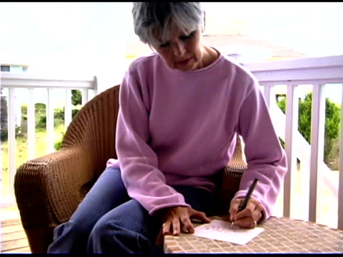 woman writing list on porch - bald head island stock videos and b-roll footage