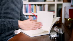 Woman Writing Notes In A Journal At Desk