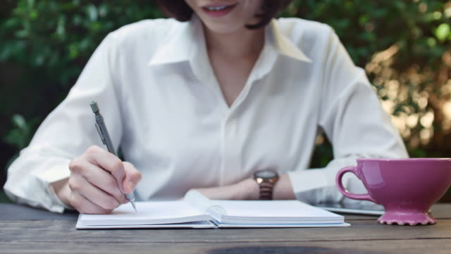 Woman writing notes in paperbook in cafe