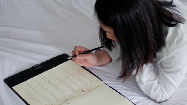 frau schreiben auf notizblock mit einem kugelschreiber, arbeiten von zuhause - schriftsteller stock-videos und b-roll-filmmaterial