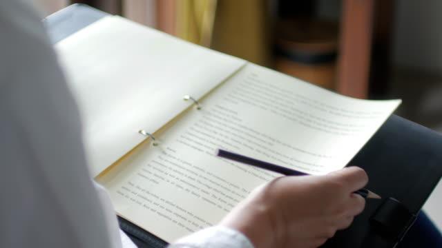 stockvideo's en b-roll-footage met vrouw schrijven op kladblok met een pen, werken thuis - ondertekenen schrijven