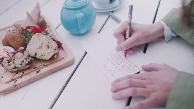 woman writing postcards - postcard stock videos and b-roll footage
