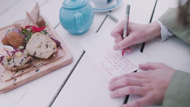 Woman writing postcards