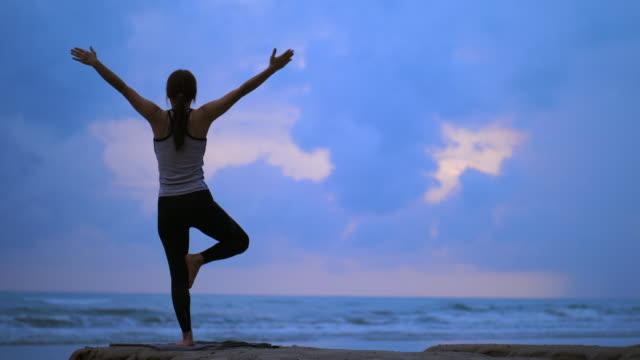 ビーチでの女性ヨガの運動 - 体を伸ばす点の映像素材/bロール