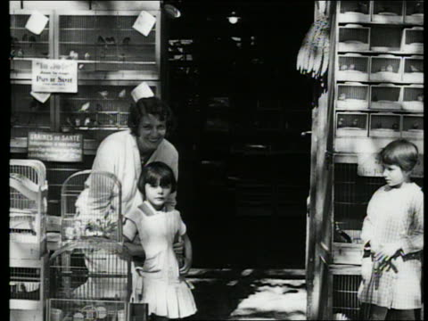 b/w 1927 woman + young girl in front of bird store / paris, france - petshop stock videos and b-roll footage