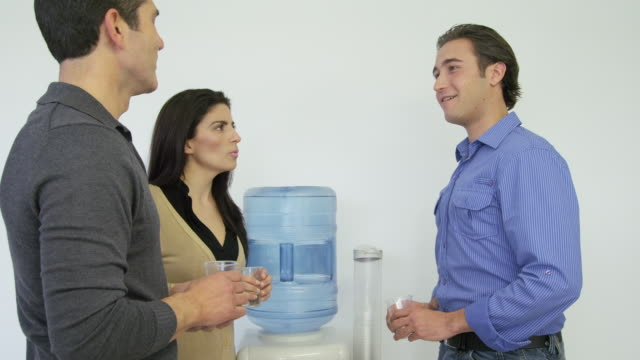 ms woman, young man and mature man having conversation at water cooler, someone out of frame makes a joke and all three erupt in laughter - coworker stock-videos und b-roll-filmmaterial