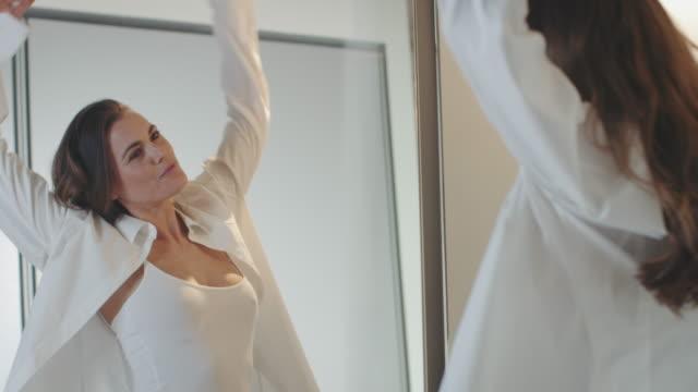 vídeos de stock, filmes e b-roll de womann posando na frente do espelho. - roupa