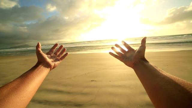 Kvinnans armar sträcka mot en vacker solnedgång