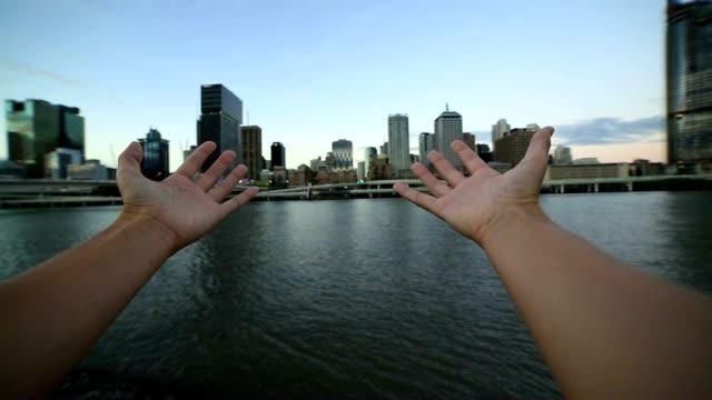 Woman's arms stretch towards Brisbane skyline