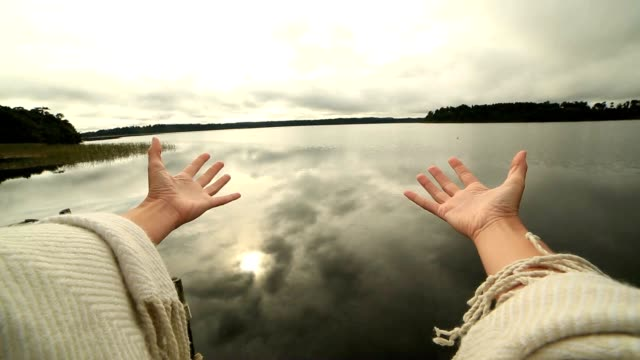 Woman's arms stretch towards mountain lake, success concept