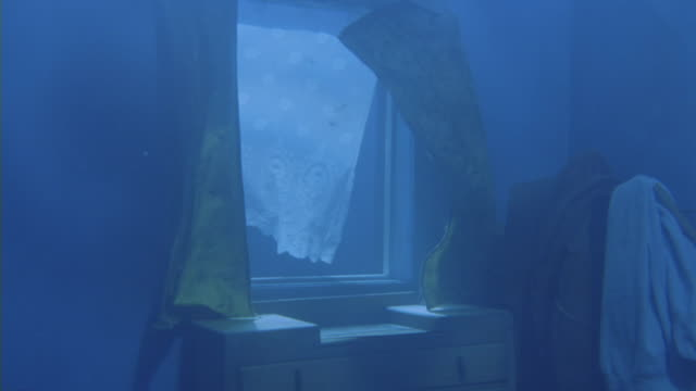 a woman's body floats in front of a curtained window in an underwater bedroom. - drowning stock videos & royalty-free footage
