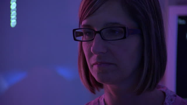 CU Woman's face in blue and pink lighting / Rockford, Illinois, USA