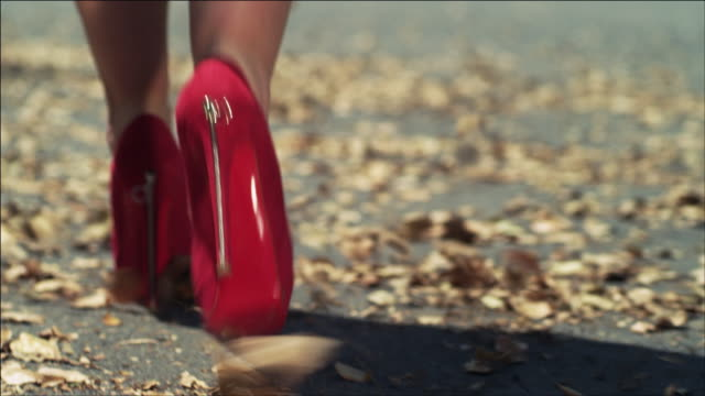 cu woman's feet from behind in red heels as she walks down suburban street covered in fallen leaves which blow in the wind - human foot stock videos & royalty-free footage