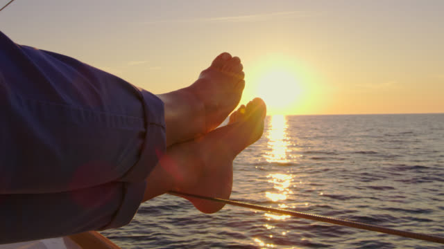slo mo woman's feet on a boat's deck at sunset - pants stock videos and b-roll footage
