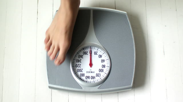 cu ha woman's feet on bathroom scale, scarborough, new york, usa - dieting stock-videos und b-roll-filmmaterial