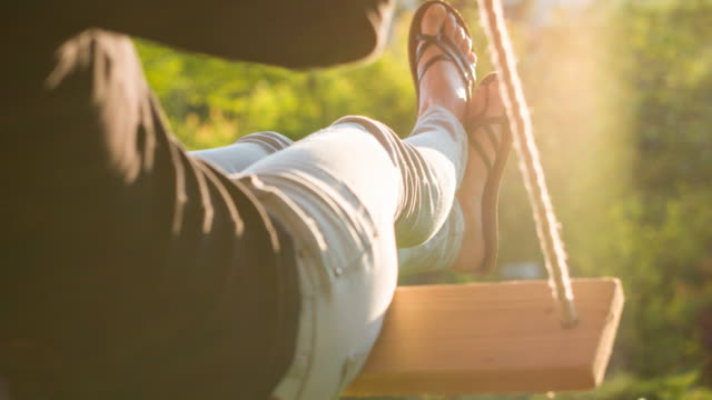 woman's feet up, swinging on a rope swing in a glade - flip flop stock videos and b-roll footage