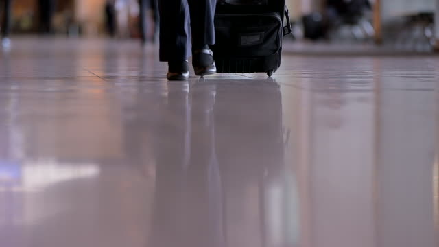 woman's feet walking in airport with suitcase - wheeled luggage stock videos and b-roll footage