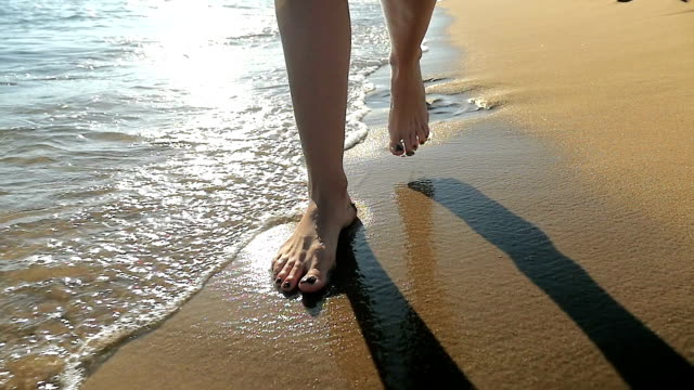 Woman's feet walking in sand