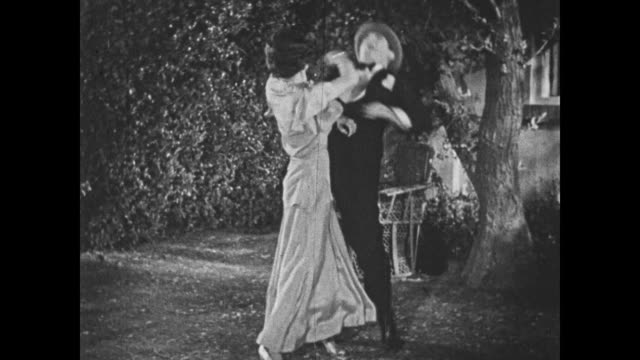 1932 a woman's fiance suffers a blow to the jaw from her impersonator - 1932 stock-videos und b-roll-filmmaterial