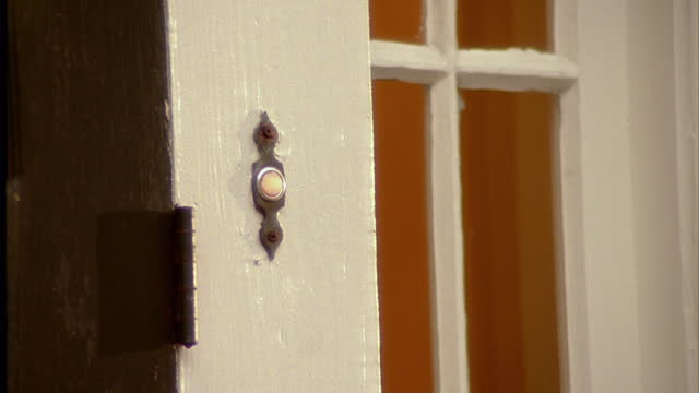 A woman's finger pushes a doorbell.