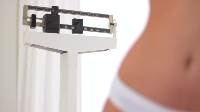 woman's flat stomach after weight loss in front of scale - hüfte stock-videos und b-roll-filmmaterial