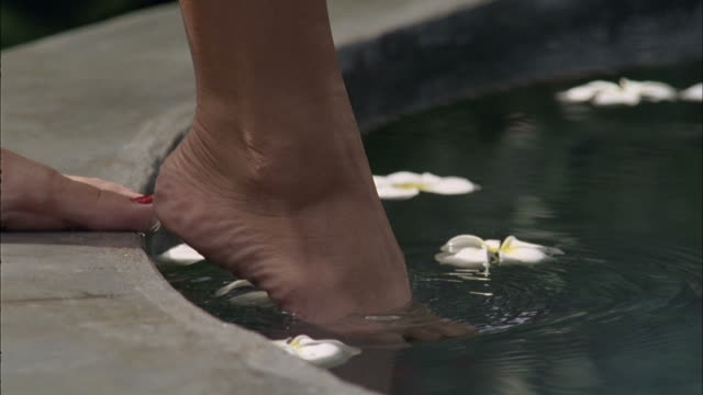 SLO MO, CU, Woman's foot tasting water with plumeria flowers, Maui, Hawaii, USA