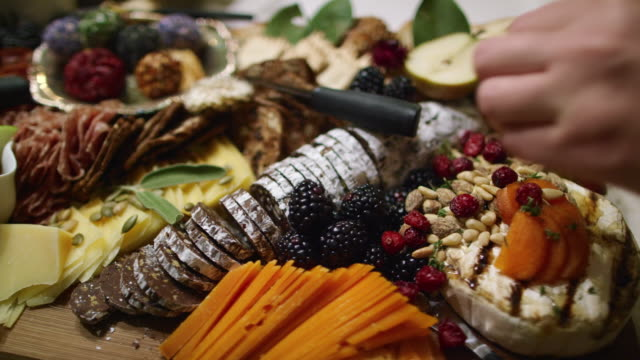 a woman's hand arranges sprigs of thyme around an appetizer charcuterie meat/cheeseboard with various fruit, sauces, and garnishes on a table at an indoor celebration/party - french food stock videos & royalty-free footage