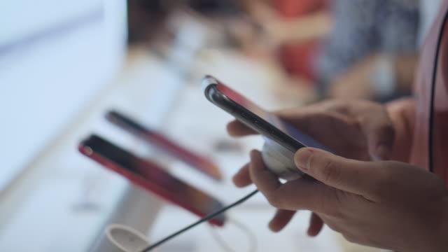 frau hand wahl für den kauf eines neuen smartphones in einem handy-shop, close-up - haushaltsmaschine stock-videos und b-roll-filmmaterial