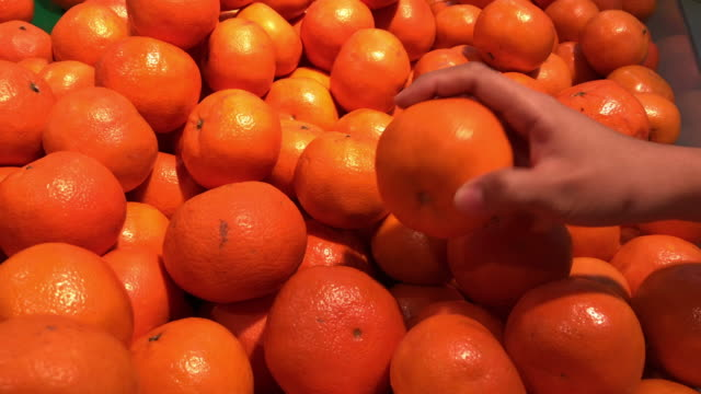 woman's hand choosing fresh orange at supermarket - quality stock videos & royalty-free footage