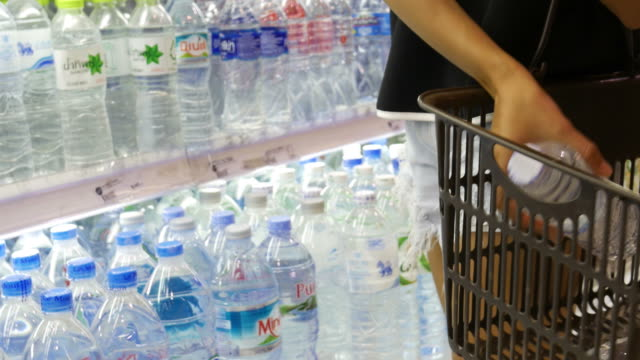 woman's hand choosing fresh water in retail store - water bottle stock videos and b-roll footage