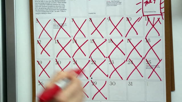 CU Woman's hand crossing out days on wall calendar, Scarborough, New York, USA