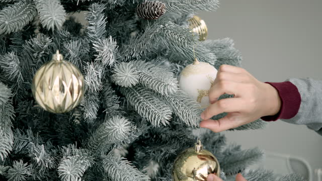 woman's hand decorating the christmas tree in the living room inside the house. - christmas tree lighting ceremony stock videos & royalty-free footage