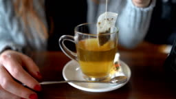 Woman's hand dipping teabag in cup at cafe