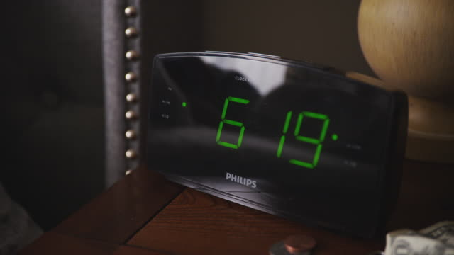Woman's hand enters frame and shuts off a digital alarm clock at 6:20 a.m.