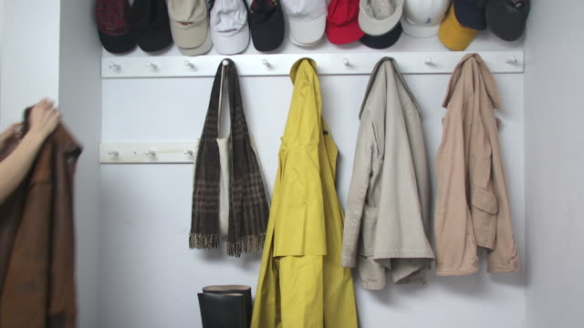 cu woman's hand hanging jacket on hook in cloakroom, scarborough, new york, usa - hanging stock videos & royalty-free footage