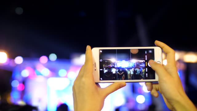woman's hand holding a smart phone during a concert - filming stock videos & royalty-free footage