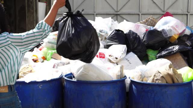 stockvideo's en b-roll-footage met een vrouw hand houden vuilniszak te gooien in de prullenbak - afvalcontainer container