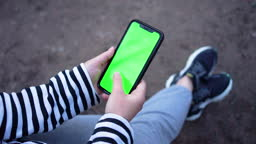 Woman's Hand Holding Modern Smartphone, touching Green Screen, swiping photos