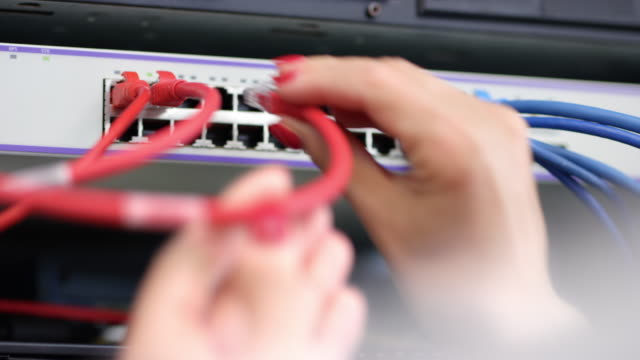 woman's hand inserting patch cables into the server - it support stock videos and b-roll footage