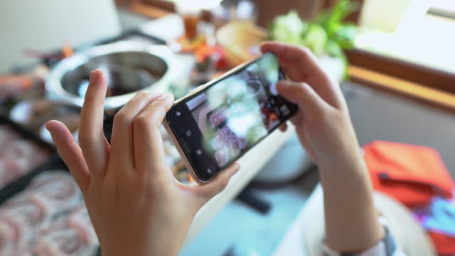 a woman's hand is taking pictures of japanese hot pot dishes with a smartphone at a restaurant during the day time - foodie stock videos & royalty-free footage