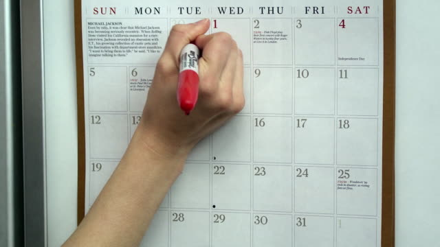 CU Woman's hand marking diet days on wall calendar, Scarborough, New York, USA