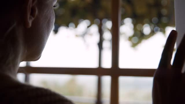 slo mo la mano della donna muove il sipario sul lato di una casa nel paese - vista posteriore video stock e b–roll